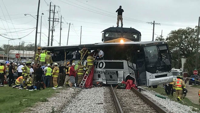 Firefighters assist injured passengers after their charter bus collided March 7, 2017, with a train in Biloxi, Miss.