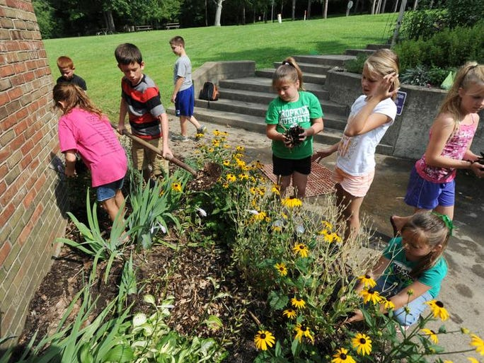 A group of youngsters mulches a garden at Blue Rock State Park on Monday. The group was part of a conservation camp run by the Muskingum Soil and Water Conservancy District.