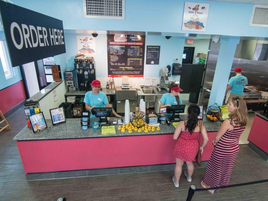Customers place an order at the front counter Tuesday at Duck Donuts on East Main Street in Newark.