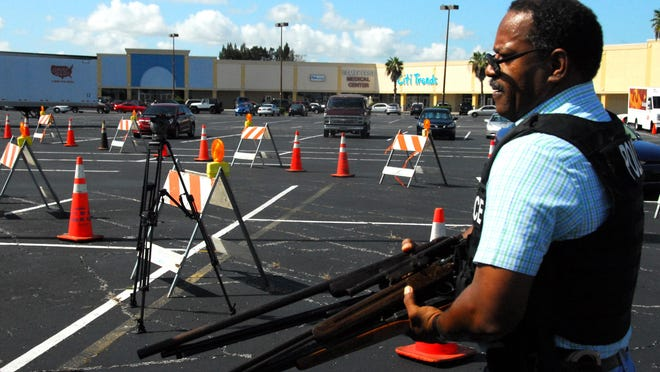In this 2011 file photo, Cocoa Det. Glenn Wade carries an armload of guns collected for the Kicks for Guns buyback program.