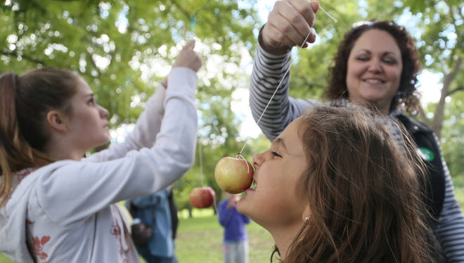 Annie Cummins, 7, of Ankeny gets help from her mom Sarah while bobbing for an apple on a string during Applefest at Living History Farms on Sept. 13, 2014.