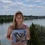 """Ashton Clinger holds a copy of """"The Call of the Osprey,"""" a young adult science book on osprey written by Dorothy Hinshaw Patent. Clinger, a 2013 Cascade High School graduate, is featured in a two-page spread in the book for research she did when she was in high school."""