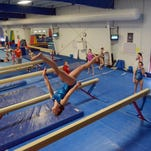 Rita Koeighbaur works out on the balance beam Thursday afternoon at Flames Gymnastics.