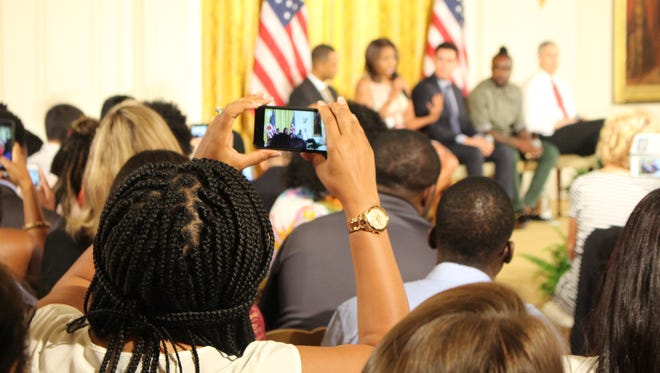 A college-bound student takes a photo of a panel featuring First Lady Michelle Obama at the 2015 Beating the Odds Summit at the White House on Thursday.