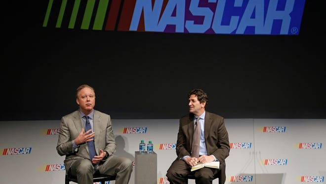 NASCAR Chairman and CEO Brian France, left, speaks to the media during the Charlotte Motor Speedway Media Tour in Charlotte, N.C., Tuesday, Jan. 19, 2016. France announced Tuesday that the Xfinity Series and the Camping World Truck Series will begin using a Chase format in 2016, mostly mirroring the playoff-style setup used to determine the Sprint Cup champion the last two years. At right is David Higdon. Vice President, Integrated Marketing Communications at NASCAR (AP Photo/Chuck Burton)