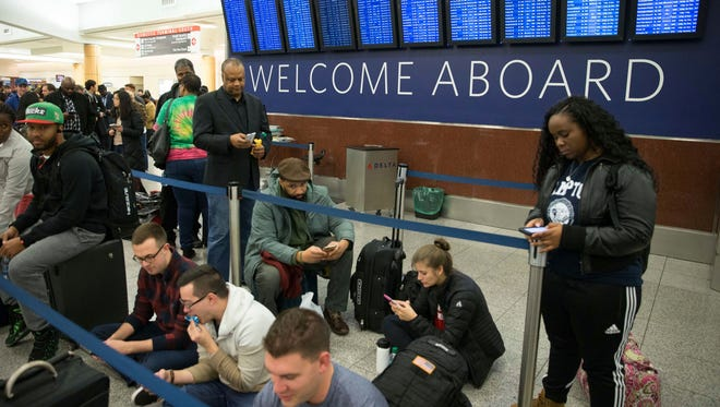 Travelers wait in line at Atlanta Hartsfield-Jackson International Airport after Delta Air Lines grounded all domestic flights due to automation issues on Jan. 29, 2017.