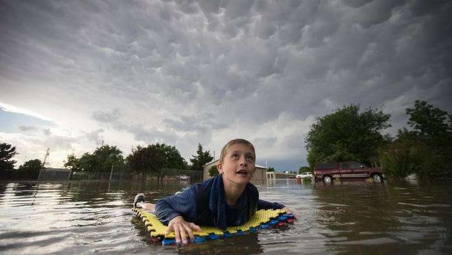 Kevin Weibe floats down his street in Scott City, Kan., while looking up at mammatus clouds after heavy rains inundated the small, western Kansas town on Tuesday, June 19, 2018.  High heat will be the main weather story in the central U.S. over the next few days.