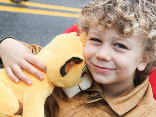 Tyler Colant, 4, happily hugs his lion that he received from Santa during the annual Christmas parade on Main Street in Boonton on November 28, 2015.