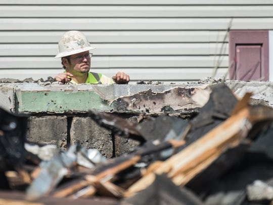 A contractor watches as Holy Temple Church of God,