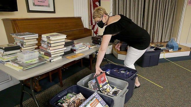 Darcie Saunier, public relations manager for the Massillon Public Library, unboxes returned books and materials that will be quarantined for three days before going back into circulation. The library reopens Tuesday to the public.