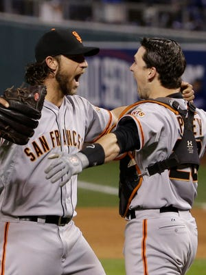 San Francisco Giants pitcher Madison Bumgarner and catcher Buster Posey celebrate after the Giants defeated Kansas City 3-2 to win Game 7 of the World Series. Bumgarner pitched five shutout innings of relief for his third victory of the series as the Giants won their third World Series in five seasons.