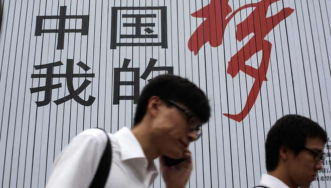 """People walk past the local government's slogan in Chinese reading: """"China My Dream"""" on Aug. 26, 2013, in Shanghai, China's financial hub."""