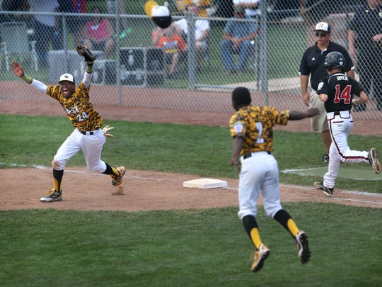 Jackie Robinson West Little League first baseman Trey Hondras, left, and winning pitcher Marquis Jackson start the celebration after the final out vs. New Albany.