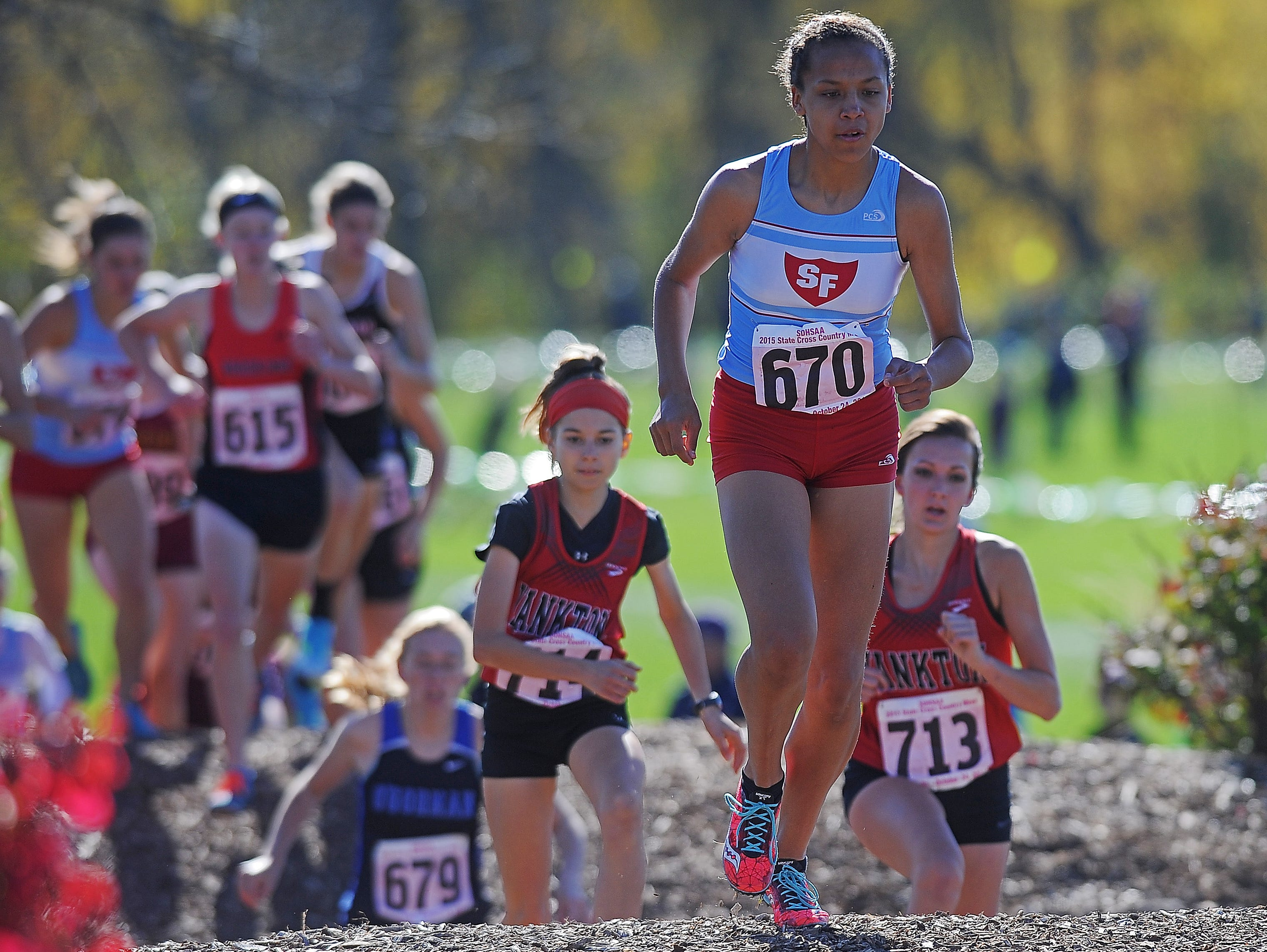 Lincoln's Jasmyne Cooper (670) runs in the girls Class AA race during the state cross country meet Saturday at Yankton Trail Park. Cooper finished ninth and Lincoln won the team title.