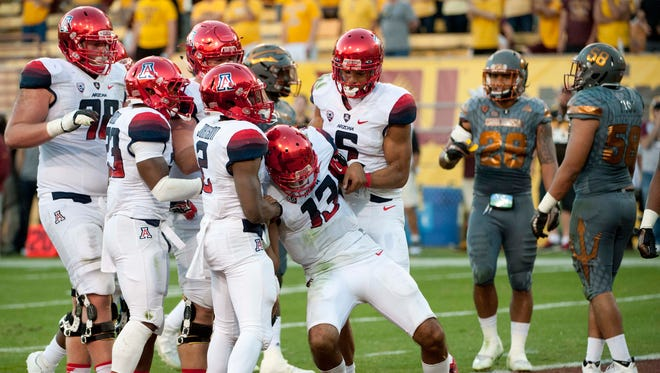 Arizona Wildcats quarterback Brandon Dawkins (13) is helped up by wide receiver Tyrell Johnson (2) and wide receiver Trey Griffey (5) during the fourth quarter of the territorial cup against the Arizona State Sun Devils at Sun Devil Stadium. The Sun Devils won 52-37.