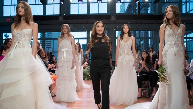 In this Friday, Oct. 7. 6, 2016 photo, designer Monique Lhuillier, center, stands with models wearing gowns from her bridal collection during bridal fashion week in New York.  (AP Photo/Mary Altaffer)