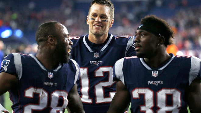 FOXBOROUGH, MA - OCTOBER 14: Tom Brady #12 of the New England Patriots celebrates with James White #28 and Kenjon Barner #38 of the New England Patriots after defeating the Kansas City Chiefs, 43-40, at Gillette Stadium on October 14, 2018 in Foxborough, Massachusetts. (Photo by Jim Rogash/Getty Images)