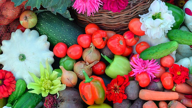 Many different vegetables with the addition of fruits and flowers laid on the pavement