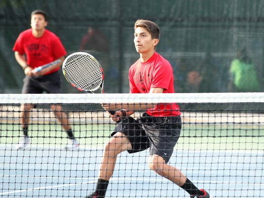Garden City's Josue Gutierrez watches after hitting the ball back across the net during boys doubles action at the  Region II-1A Tennis Tournament Thursday at Bentwood Country Club.