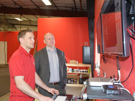 Derek Grenfell, left, shows Caleb Frostman, DCEDC director, the computer system for CrossFit Armati Wednesday, March 29, 2017.