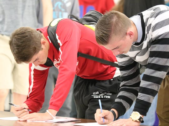 Two students at Oak Harbor High School fill out an application during the second annual Summer Job Fair on Wednesday.