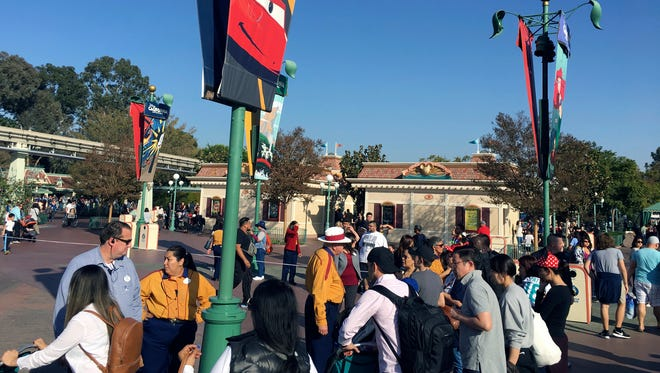 Disneyland park workers stop people from approaching the entrance as the turnstiles are roped off at the entrance of the park in Anaheim, Calif., Wednesday, Dec. 27, 2017.