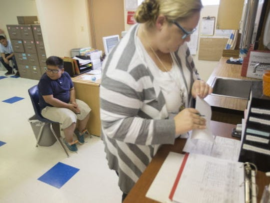 Nurse Jacqueline Leeburg looks through forms while