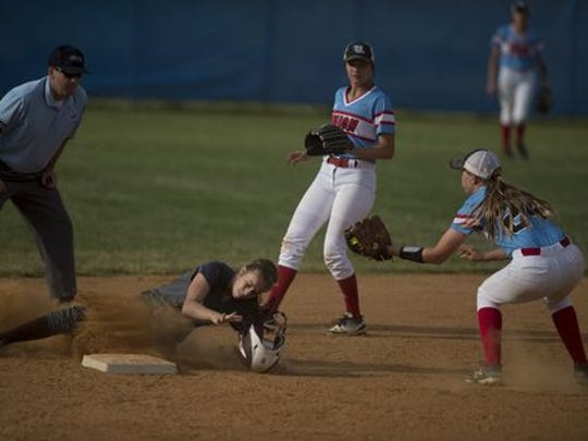 Henderson County's Kaitlyn McCormick has her helmet knocked off by the tag of Union County's Taylor Windell while caught stealing during their sectional game at Union County High School Monday evening.