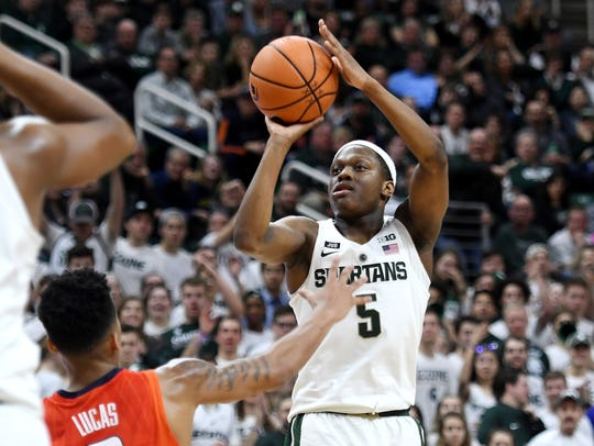 Michigan State's Cassius Winston, right, shoots over