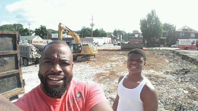 Abdulla Jamison, left, and his son, Ayura, 13, stand at the site of the former Dutch Club. Jamison bought the property and tore down the old club, which for years did not admit African-Americans, to build a new auto service business.