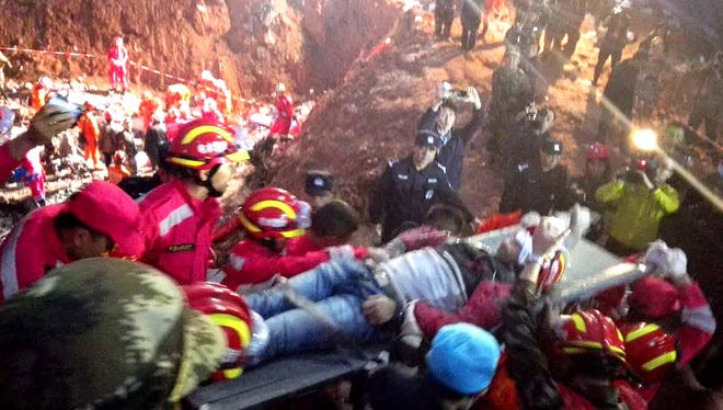 Rescuers carry Tian Zeming after he was pulled from debris on Dec. 23 more than 60 hours after a giant flow of mud and construction waste engulfed buildings in Shenzhen, China.