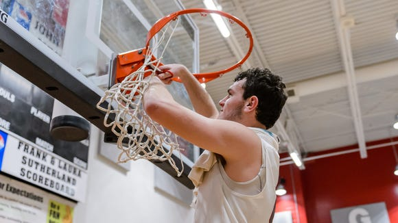 Wade Hampton senior Will Edwards cuts down the net after the Region 2-AAAAA champion Generals' 58-37 win over Riverside Friday night. Edwards scored 31 points, including his 1,000th career point.