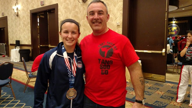 Savannah Garcia and her dad and coach, Christopher Garcia, pose with her medal at the World Karate Commission World Championships in Orlando.