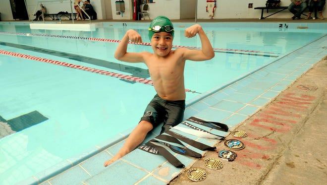 Gavin Chavira, 6, shows off his medals at Veterans Park in Northeast El Paso.