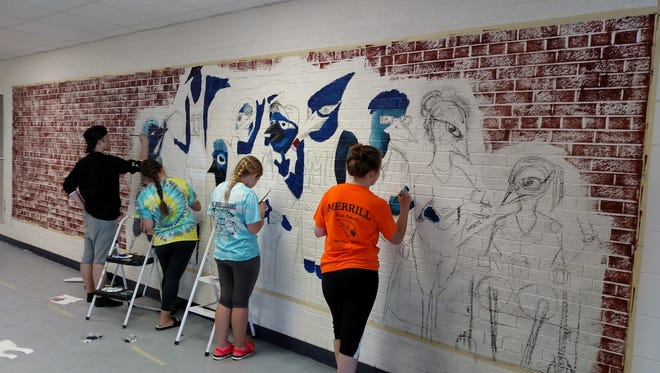Merrill High School art students are shown in the beginning phases of painting their graffiti mural.