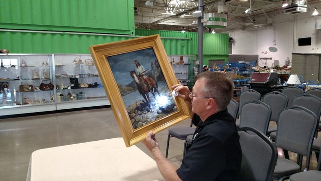 Because so many international high-profile cases of fraud have been reported over the years, reputable dealers and auction houses are taking extra steps to authenticate art. Pictured here: Auctioneer Erik Hoyer examines a painting by Frank Tenney Johnson.