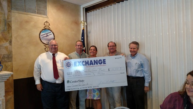 Exchange Club of Vero Beach Christmas Tree Committee Chairman Brad Smith, left, gives a check for $12,500 to Jason Shaver, president of the Vero beach High School Band Booster Club. Also pictured are Booster Club member Missy Gloetznep, Exchange Club President Vance Brinkerhoff and Mike Tupek, Booster Club member. The money represents the Boosters'portion of profits from helping the Exchange Clubsell Christmas trees. The band helps the Exchange Club with selling Frasier fir Christmas trees from the Friday after Thanksgiving until the Saturday before Christmas. The lot where the sale is held has been loaned by the Indian River Medical Center on 37th Street for the past few years. Trees that are not sold by the last day are donated to the Gifford Youth Achievement Center to be given to needy families.