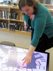 Outreach librarian Rebecca Hopman uses a touch screen table in the Rakow Research Library at the Corning Museum of Glass.