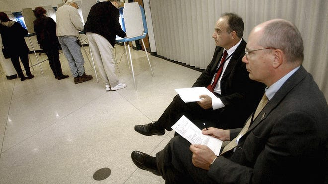 Parliamentarians Goran Lennmarker, right, of Sweden and Stavros Evagorow, of Cyprus, observe the American voting process as voters cast their ballots at Robbinsdale City Hall in Robbinsdale, Minn., in 2004.