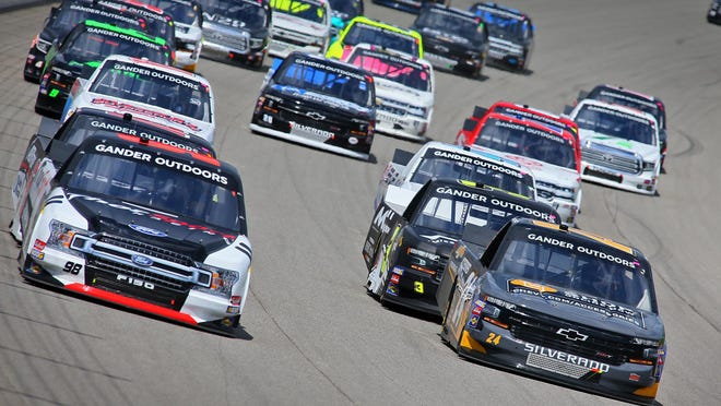 Grant Enfinger, left, and Brett Moffitt, right, lead a pack after a restart during the Corrigan Oil 200 in 2019.