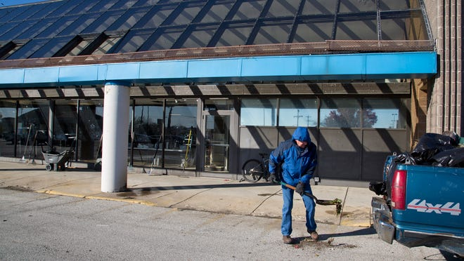 Volunteer Oscar Harmon shovels some of the dirt and debris around the former Pay Less store off of Old U.S. 231 Nov. 1 in Lafayette. First Assembly Community Ministries is moving forward with its plan to renovate the former market into a community center. About 50-75 volunteers helped Saturday morning to clean the place up.