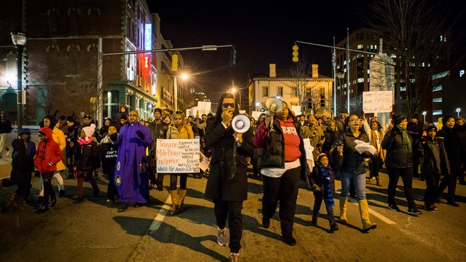 Fred Green chants through a bullhorn as he leads protesters down King Street to Fourth Street in Wilmington on Monday evening.