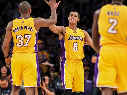 Los Angeles Lakers forward Metta World Peace, left, celebrates with Jordan Clarkson, center, during a timeout in the second half of an NBA basketball game against the Orlando Magic Tuesday, March 8, 2016, in Los Angeles. The Lakers won 107-98. (AP Photo/Ringo H.W. Chiu)