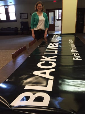 Reverend Sharon K. Dittmar, Senior Minister, at First Unitarian Church, Avondale, shows the banner that the congregation will hang on its building Sunday.