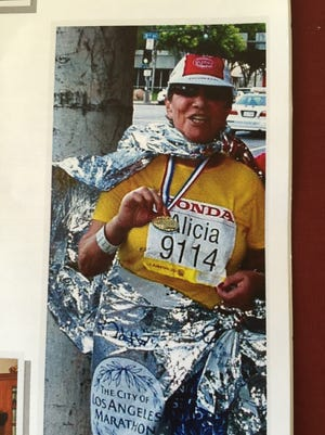 Alicia Guerrero celebrates completing her first marathon at age 77. Encouraged by her husband, Ray Arevalo, she completed three Los Angeles Marathons before she died suddenly in 2015.