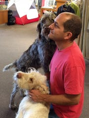 Richard Kassar with his dogs in his store, Benchmark