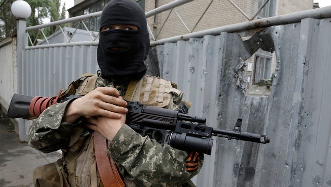 A pro-Russian fighter stands near a damaged gate at an Ukrainian military unit  captured by pro-Russian fighters in the city of Donetsk, Ukraine.