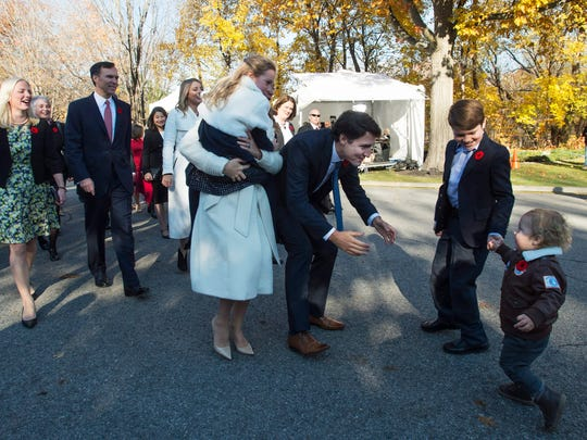Hadrien Trudeau runs into his father's arms as Prime Minister-designate Justin Trudeau, his wife Sophie Gregoire-Trudeau, holding daughter Ella-Grace and their oldest son Xavier arrive at Rideau Hall with Trudeau's future cabinet to take part in a swearing-in ceremony in Ottawa on Wednesday, Nov.  4, 2015.