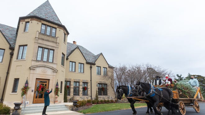 Santa leads a horse-drawn carriage alongside members of 3C Carriage Service, Kansas Forestry Association and Kansas Christmas Tree Growers Association to deliver a Korean fir tree to Cedar Crest, the governor's mansion, on Tuesday morning.