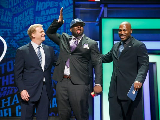Alabama's Jarran Reed poses for photos with NFL Commissioner Roger Goodell, left, and former NFL player Shaun Alexander after being selected by the Seattle Seahawks as the 49th pick in the second round of the 2016 NFL football draft, Friday, April 29, 2016, in Chicago. (AP Photo/Charles Rex Arbogast)